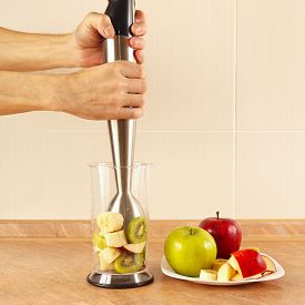 stock photo of blender  - Hands are going to mix fruit cocktail in a blender - JPG